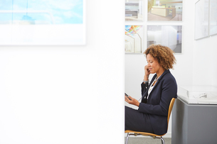 Female designer sitting in office listening to earphonesの写真素材 [FYI03580430]
