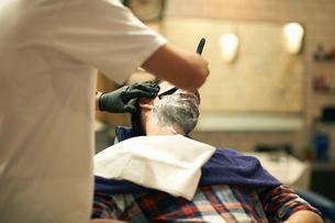 Hairdresser in barbershop giving customer wet shaveの写真素材 [FYI03580754]