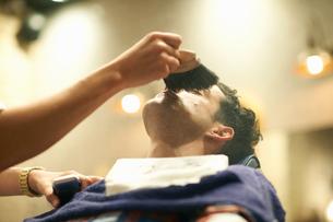 Hairdresser in barbershop giving customer wet shaveの写真素材 [FYI03580757]