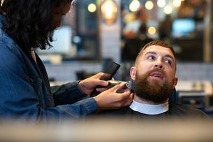 Hairdresser in barbershop trimming customer's beardの写真素材 [FYI03580764]