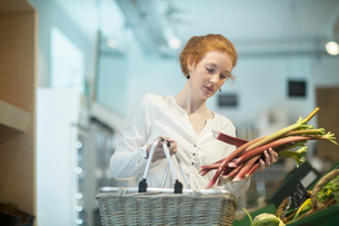 Woman in shop holding shopping basket and rhubarbの写真素材 [FYI03580842]