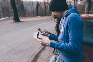 Hiking couple looking at map and smartphone on forest roadside, Monte San Primo, Italyの写真素材 [FYI03581114]