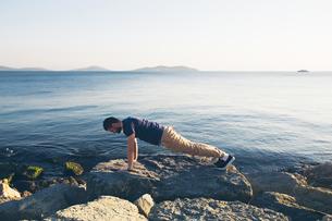 Man doing push ups on rocks by sea, Istanbul, Turkeyの写真素材 [FYI03581304]