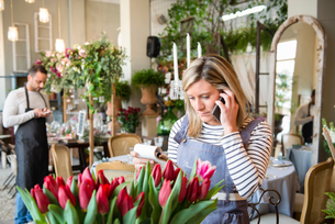 Florist in flower shop, using smartphone, taking flower orderの写真素材 [FYI03581362]