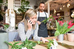 Female florist talking on smartphone, male colleague preparing flower order behind herの写真素材 [FYI03581369]