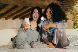 Friends sitting on bed looking at smartphone smilingの写真素材 [FYI03581512]