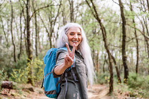 Portrait of mature female backpacker giving peace sign in forest, Scandicci, Tuscany, Italyの写真素材 [FYI03581675]