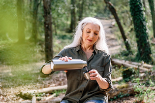 Mature female backpacker pouring drinks flask in forest, Scandicci, Tuscany, Italyの写真素材 [FYI03581678]