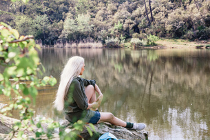 Mature female backpacker looking out from river bank in forest, Scandicci, Tuscany, Italyの写真素材 [FYI03581679]