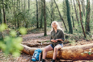 Mature female backpacker sitting on log in forest, Scandicci, Tuscany, Italyの写真素材 [FYI03581680]