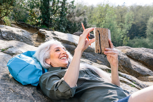Mature female backpacker reclining on rock in forest, Scandicci, Tuscany, Italyの写真素材 [FYI03581681]