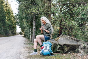 Mature female backpacker looking at smartphone on forest road, Scandicci, Tuscany, Italyの写真素材 [FYI03581682]
