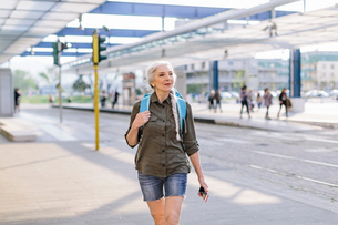 Mature female backpacker walking in bus station, Scandicci, Tuscany, Italyの写真素材 [FYI03581683]