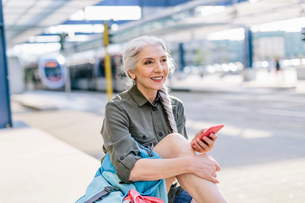 Mature female backpacker holding smartphone in bus station, Scandicci, Tuscany, Italyの写真素材 [FYI03581684]
