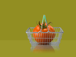 Tomato in miniature shopping basket on green backgroundの写真素材 [FYI03581688]