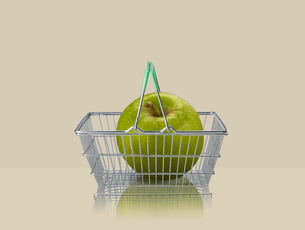 Granny smith apple in miniature shopping basket on beige backgroundの写真素材 [FYI03581689]
