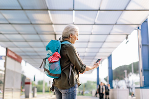 Mature female backpacker looking at smartphone in bus station, Scandicci, Tuscany, Italyの写真素材 [FYI03581692]