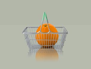 Orange in miniature shopping basket on grey backgroundの写真素材 [FYI03581695]