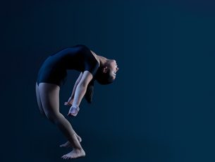 Low key shot of young female dancer standing and bending over backwardsの写真素材 [FYI03581714]