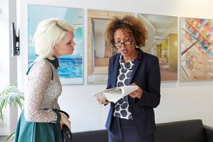 Female designer explaining blueprint to female client in office lobbyの写真素材 [FYI03581723]