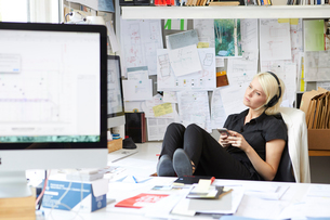 Female designer with feet up at desk listening to headphone musicの写真素材 [FYI03581727]