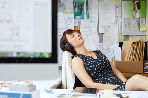 Female designer at office desk listening to headphone music  with eyes closedの写真素材 [FYI03581731]