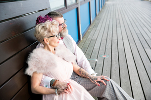 1950's vintage style couple sitting on pier benchの写真素材 [FYI03581826]