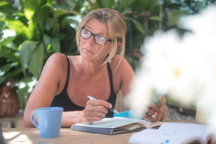 Mature woman writing diary at table in garden, Majorca, Spainの写真素材 [FYI03581905]