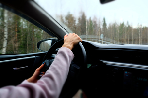 Woman driving left hand drive vehicle, close-upの写真素材 [FYI03581939]
