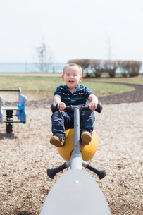 Male toddler playing on seesaw in coastal parkの写真素材 [FYI03582064]