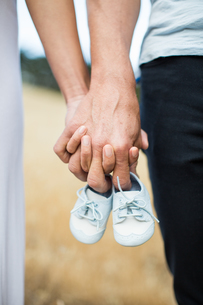 Couple holding hands, man holding baby shoes on fingers, close-upの写真素材 [FYI03582110]