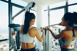Two young women working out in gym, using gym equipmentの写真素材 [FYI03582198]