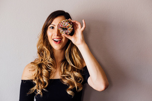 Portrait of young woman with long blond hair holding doughnut hole over eyeの写真素材 [FYI03582346]