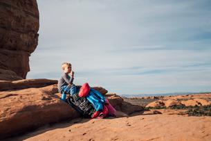 Boy sitting on rock in desert, eating snack, Moab, Utah, USAの写真素材 [FYI03582407]