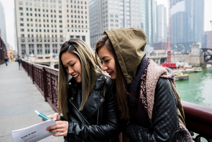 Two friends, outdoors,  looking at smartphone, smilingの写真素材 [FYI03582477]