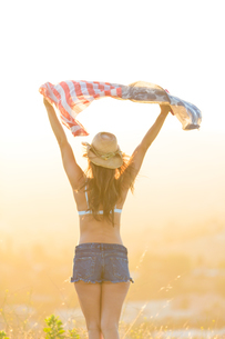 Woman wearing bra top and denim shorts, holding American flag above head, rear viewの写真素材 [FYI03582481]