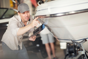 Man checking bodywork on boat in repair workshopの写真素材 [FYI03582587]