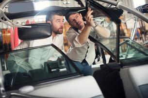 Two men checking motor boat in repair workshopの写真素材 [FYI03582594]