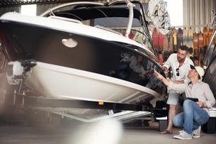 Two men checking motor boat bodywork in repair workshopの写真素材 [FYI03582598]