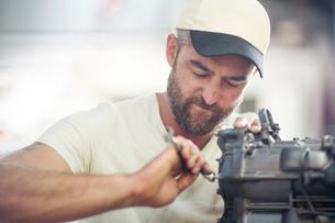 Man repairing outboard motor in boat repair workshopの写真素材 [FYI03582600]