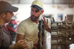 Two men repairing outboard motor in boat repair workshopの写真素材 [FYI03582601]