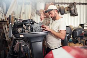 Man repairing outboard motor in boat repair workshopの写真素材 [FYI03582606]