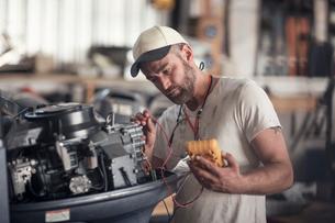 Man using machine to test outboard motor in boat repair workshopの写真素材 [FYI03582610]