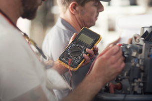 Man using machine to test outboard motor in boat repair workshopの写真素材 [FYI03582611]