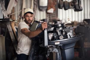 Man testing outboard motor in boat repair workshopの写真素材 [FYI03582615]