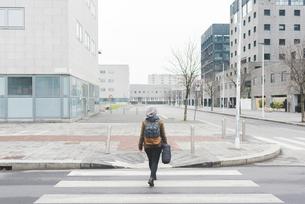 Rear view of female backpacker walking over city pedestrian crossingの写真素材 [FYI03582668]