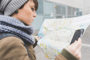 Female backpacker with smartphone looking at map in cityの写真素材 [FYI03582669]