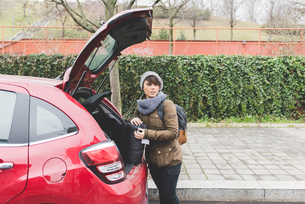 Female backpacker removing sleeping bag from car boot in cityの写真素材 [FYI03582670]