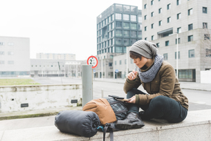 Female backpacker sitting on wall looking at notebookの写真素材 [FYI03582671]