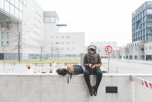 Female backpacker sitting on wall selecting smartphone musicの写真素材 [FYI03582672]